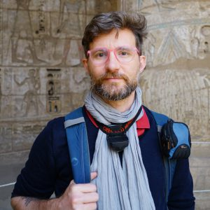 Flounder Lee looking at the camera, slight smile, wearing a backpack, scarf, glasses, standing in front of Egyptian hieroglyphics