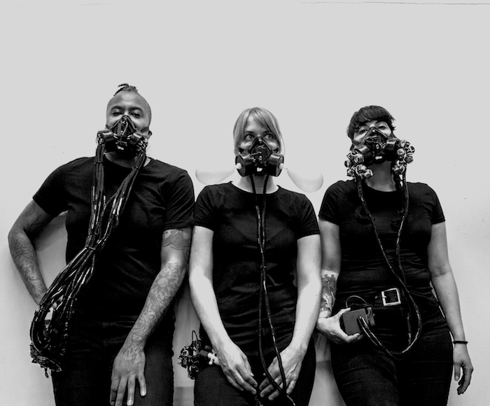 Three people wearing custom wearable instruments made of gas masks