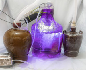 Three bottles of various makes and sizes with tubes and wires running around. The middle bottle has water, air bubbles, and light